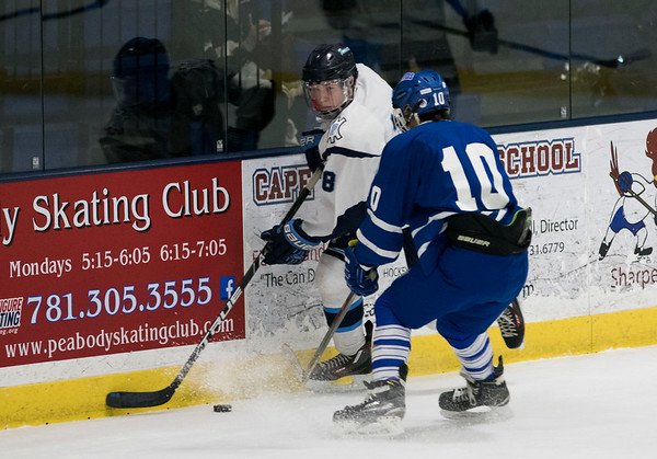 SAM GORESH/Staff photo. Peabody senior Sal Zarro looks to pass the puck as Danvers senior Robert Tibbetts races to stop him on defense in their game at McVann-O'Keefe Rink. 1/10/17