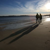 Matt and Michaela Russo, of Beverly, create long shadows on the sand at Dane Street Beach in Beverly