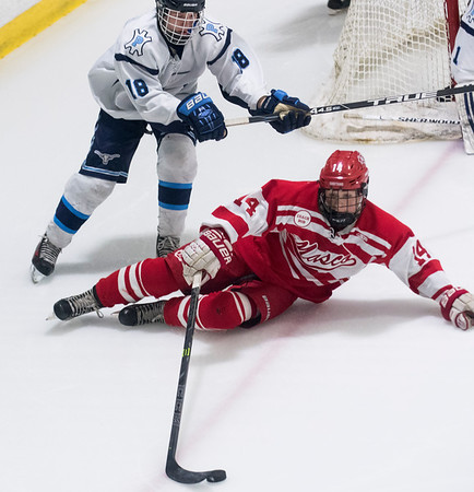 SAM GORESH/Staff photo. Masconomet sophomore Brendan Driscoll attempts to maintain control of the puck as Peabody freshman Kyle McCarthy comes behind him on defense in the inaugural 'Can Do' Classic. The game ended in a 3-3 tie. 1/2/17