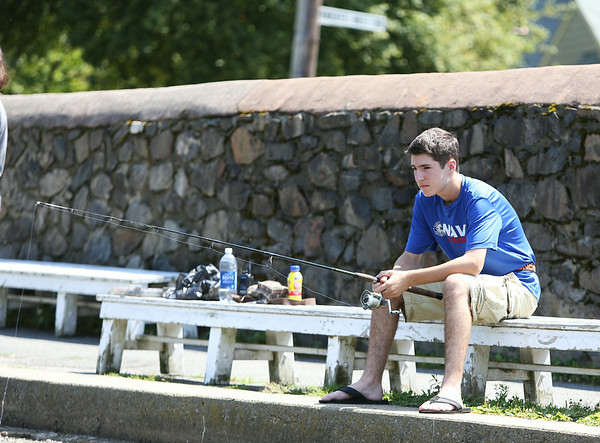 Tyler Merullo, of Marblehead, waits patiently while fishing at Redd's Pond in Marblehead on Monday afternoon. DAVID LE/Staff photo. 7/28/14.