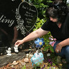 KEN YUSZKUS/Staff photo. Annmarie Schieding holds one of two angels replacing the missing angels and figurines stolen from her daughter's grave at Oak Grove Cemetery.  7/01/14