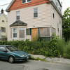 KEN YUSZKUS/Staff photo. The boarded up house at 11 Holten Street in Peabody.   7/14/14