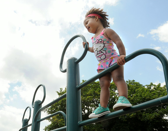 KEN YUSZKUS/Staff photo. Bunny MacIntosh, 2, of Danvers, fearlessly climbs to the top of the playground equipment at Dane Street Beach in Beverly.   7/7/14