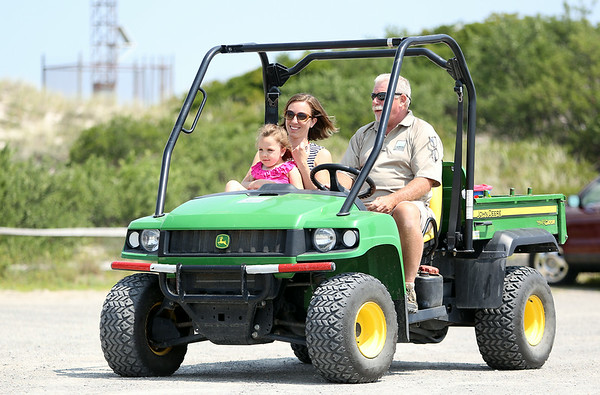 Alex Pecci, and her daughter Chloe, 5, of Plaistow, NH, get a ride down to the beach from Cranes Beach Ranger Larry Eaton on Thursday morning. Pecci wrote a letter of thanks to the Reservation after Eaton helped get them down to the beach with the cart as Chloe has Spina Bifida, making it difficult for her to walk. A day after the letter was received, the Reservation got a generous donation of a Mobi-Chair, a chair designed to allow the disabled get onto the beach and even float in the water. DAVID LE/Staff photo. 7/31/14.
