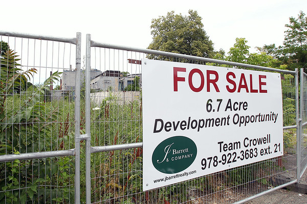 A For Sale sign has been posted on a fence on the property of the old Salem Oil an Grease Factory located at 60 Grove Street in Salem. DAVID LE/Staff photo. 7/10/14.