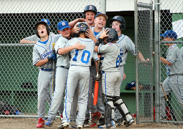 The Danvers American all-star team mobs Joe Thibodeau (10) after he hit a solo home run on Tuesday evening at Harry Ball Field in Beverly. DAVID LE/Staff photo. 7/8/14.
