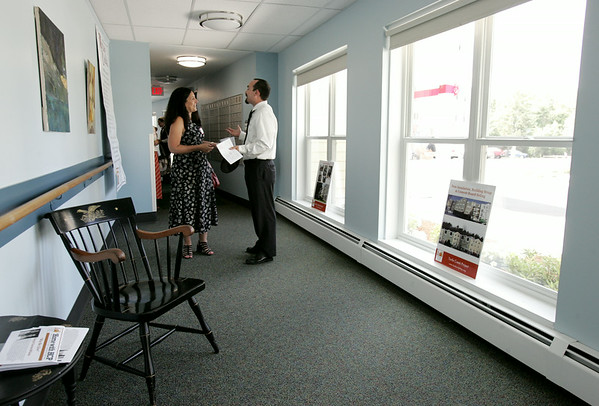 KEN YUSZKUS/Staff photo. Housing director Yvonne Graham speaks with executive director Andrew DeFranza in the renovated hallway with new energy efficient easy open windows, new paint, and new carpeting during the post construction festivities at Turtle Creek in Beverly.  7/9/14