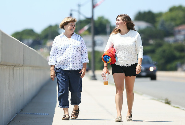 Danielle Langelier, right, visiting home from Chicago, walks along the Causeway in Marblehead and talks with her mother, Kathy Carley, of Marblehead, on Monday afternoon. DAVID LE/Staff photo. 7/21/14.