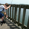 KEN YUSZKUS/Staff photo. Thomas Grimes, 10, of Salem, NH, fishes off the Beverly wharf with his brothers and grandmother.   7/8/14