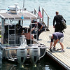 Two divers from the State Police Underwater Recovery Team board the Marblehead Harbormaster's boat as they took to the water to help in the search for a missing diver off Children's Island on Tuesday afternoon. DAVID LE/Staff photo. 7/22/14.