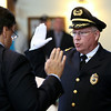 Peabody Police Chief Tom Griffin raises his right hand while being sworn into office by Peabody City Clerk Tim Spanos in the Wiggin Auditorium at Peabody City Hall on Thursday afternoon. DAVID LE/Staff photo. 7/24/14.