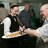 KEN YUSZKUS/Staff photo. Sarah McArdle offers Tom Wetson hors d'oeuvres during the post construction festivities at Turtle Creek in Beverly.  7/9/14