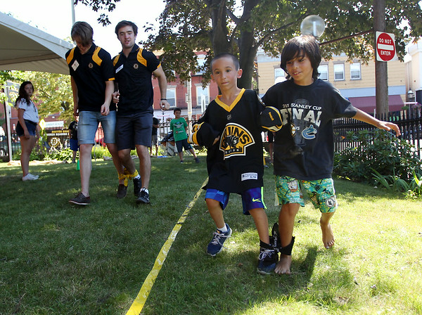 Seven-year-old Anthony Costanzo, left, and nine-year-old Marco Schirripa, both of Peabody, race ahead of Boston Bruins prospects Simon Norberg, and Michael Doherty, during a three-legged race on Friday afternoon. DAVID LE/Staff photo. 7/11/14.