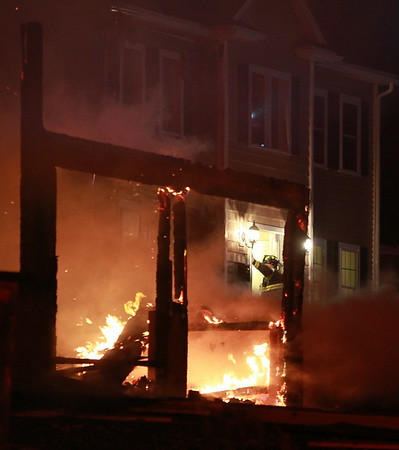 A firefighter enters the door of a house on Folger Ave, as the remnants of another house burns in the foreground,  where a 3-alarm fire broke out late on Sunday evening. DAVID LE/Staff photo. 7/13/14.