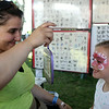 Eight-year-old Lily Bowen, of Marshfield, smiles as she looks in the mirror at her finished air brush tattoo done by Betty Lopes, of Amazing Face Art, during the first Salem Willows Seafood Festival on Saturday afternoon. DAVID LE/Staff photo. 7/12/14.