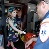 Three-year-old Hazel Cormier, of Ipswich, smiles at EMT Brian Moran, of Action Ambulances, while she has her oxygen levels checked during Vehicle Day at the Ipswich Public Library on Friday morning. DAVID LE/Staff photo. 7/25/14.