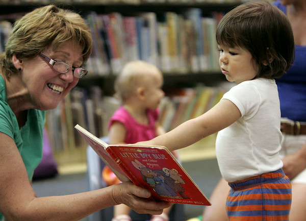 KEN YUSZKUS/Staff photo. Logan Wild, 15 months, takes a close look at a book read by Chrissy Ierardi in the Wee Folks program held at the Abbot Public Library .     7/11/14