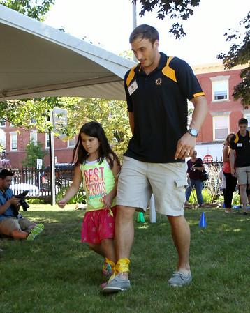 Six-year-old Avery Skinner and Boston Bruins prospect Kyle Baun hurry towards the finish line in a three-legged race on Friday afternoon at the Peabody Institute Library. DAVID LE/Staff photo. 7/11/14.
