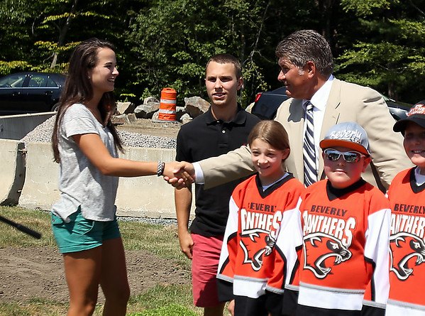 Beverly rising junior Anna Hayden, left, shakes hands with Boston Bruins legend Ray Bourque, as recently graduated senior Connor Irving looks on, at a groundbreaking ceremony for the new ice hockey rink at Endicott College, which will be named the Raymond J. Bourque Arena and is set to be completed in fall 2015. DAVID LE/Staff photo. 7/29/14.