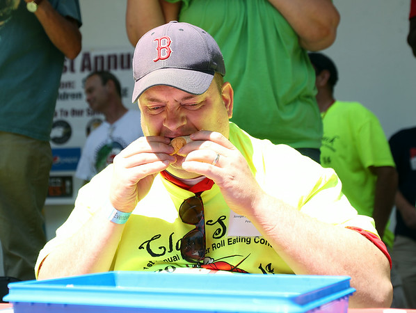 Joseph Kameese, of Peabody, bites deep into a lobster roll during the Lobster Roll Eating Contest during the first Salem Willows Seafood Festival on Saturday afternoon. Kameese won the competition, downing 9 lobster rolls in 10 minutes. DAVID LE/Staff photo. 7/12/14.