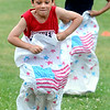 KEN YUSZKUS/Staff photo. Aidan Silva, 7, won the sack race for 7-10 year-olds during July 4th activities at Peabody's Welch School playground. His sister Kailey, 9, in the background, won 2nd place. 7/4/14