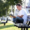 Orlando Estevez, of Beverly, sits on a bench at Independence Park in Beverly on Monday afternoon reading George R.R. Martin's Game of Thrones. DAVID LE/Staff photo. 7/28/14.