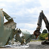 An excavator with a shearing mechanism attached, operated by a member of JDC Demolition, rips down the outer wall of the B5 tank, an old oil tank inside the Salem Power Plant facility on Wednesday afternoon. The B5 tank is the first of the old oil tanks on the site to be taken down and will take approximately two weeks until it is completely gone. DAVID LE/Staff photo. 7/30/14.