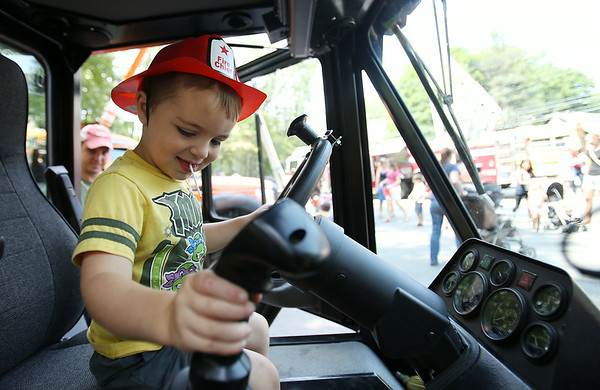 Three-year-old Evan Butler, of Ipswich, plays around in the cabin of a construction vehicle during Vehicle Day at the Ipswich Public Library on Friday morning. DAVID LE/Staff photo. 7/25/14.