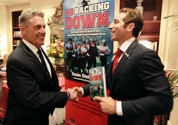 "Former Salem High School quarterback and current NFL Agent Sean Stellato, right, shakes hands with his old coach Ken Perrone, at a gala and book signing for Stellato's new book ""No Backing Down"" a book on the 1994 Salem High School Super Bowl football team. DAVID LE/Staff photo. 7/11/14."