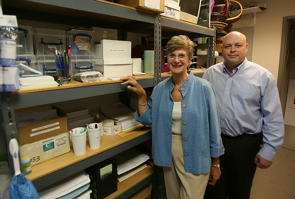 John Somes, Executive Director of the Greater Beverly Chamber of Commerce, stands with Nancy Black, of Organization Plus, who helped the Chamber organize and rearrange shelves after their move to the Cummings Center in Beverly. DAVID LE/Staff photo. 7/28/14.