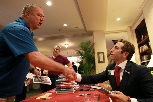 "John Jodoin, of Salem, shakes hands with NFL Agent Sean Stellato, of Peabody, at a gala and book signing for Stellato's new book ""No Backing Down"" a book on the 1994 Salem High School Super Bowl football team. DAVID LE/Staff photo. 7/11/14."