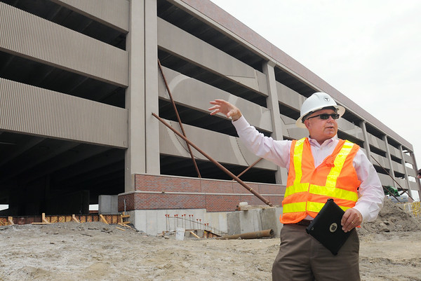 KEN YUSZKUS/Staff photo. Project manager George Doherty speaks about the new Salem MBTA parking garage under construction in the background.   7/3/14