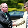 Boston Bruins legend Ray Bourque, right, shakes hands with Endicott College Athletic Director Brian Wylie, at a groundbreaking ceremony for the new ice hockey rink at Endicott College, which will be named the Raymond J. Bourque Arena and is set to be completed in fall 2015. DAVID LE/Staff photo. 7/29/14.