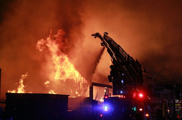 Flames shoot through the roof of a house on Folger Ave where a 3-alarm fire broke out late on Sunday evening. DAVID LE/Staff photo. 7/13/14.
