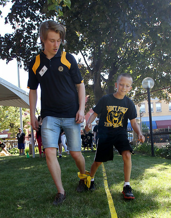 Nine-year-old Logan Tracia and Boston Bruins prospect Simon Norberg, participate in a three-legged race on Friday afternoon at the Peabody Institute Library. DAVID LE/Staff photo. 7/11/14.