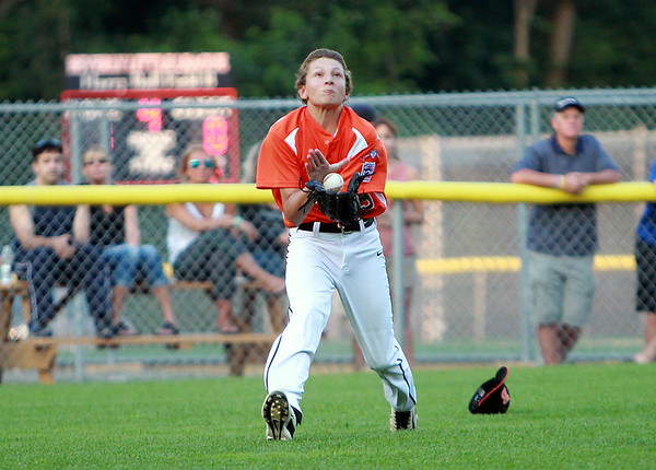 Beverly center fielder Mike Anderson makes a basket catch on a short popup after losing his hat to retire a Danvers American batter on Tuesday evening at Harry Ball Field in Beverly. DAVID LE/Staff photo. 7/8/14.