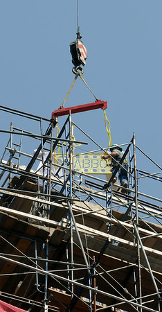 KEN YUSZKUS/Staff photo. Rigger Chet McWhinnie guides the weathervane into place as it is installed on top of the tower at Abbot Hall in Marblehead. 7/2/14