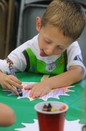 KEN YUSZKUS/Staff photo. Andrew Lubas, 4, of Salem decorates a fan at the craft table during the Fizz, Boom, Party held at the Salem Public Library. 7/1/14