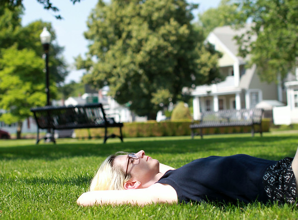 Molly Hoisington, a graduate of Monserrat College of Art, lies in the shade on Beverly Common trying to stay cool on a very hot July afternoon. DAVID LE/Staff photo. 7/23/14.