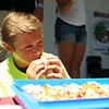 Fourteen-year-old Josh Bates, of Beverly, bites into a lobster roll during the Lobster Roll Eating Contest during the first Salem Willows Seafood Festival on Saturday afternoon. DAVID LE/Staff photo. 7/12/14.