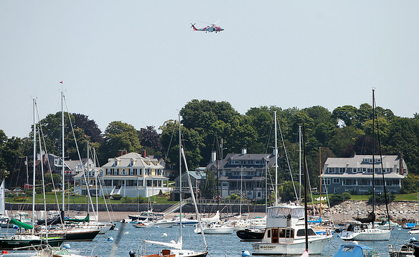 A Coast Guard chopper patrols the skies over Marblehead Harbor on Tuesday afternoon after a diver went missing near Children's Island earlier Tuesday morning. DAVID LE/Staff photo. 7/22/14.