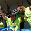 Joseph Kameese, of Peabody center, raises his arms in celebration, while being congratulated by Mike Sullivan, of Salem, right, as time ticks down during the Lobster Roll Eating Contest during the first Salem Willows Seafood Festival on Saturday afternoon. DAVID LE/Staff photo. 7/12/14.