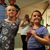 Meghan, 8, and Riley Fessenden, 7, smile as a quotation painted on the wall is read. With the help of 75 volunteers, a nonprofit called Special Spaces Boston, did a three-day makeover of the downstairs playroom for Riley Fessenden and her brothers and sisters. DAVID LE/Staff photo. 7/26/14.
