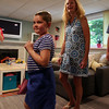 Seven-year-old Riley Fessenden smiles as a secret door is revealed as her mother Kamie smiles in the background. With the help of 75 volunteers, a nonprofit called Special Spaces Boston, did a three-day makeover of the downstairs playroom for Riley Fessenden and her brothers and sisters. DAVID LE/Staff photo. 7/26/14.