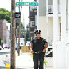 Salem Patrolman Victor Ruiz walks down Leavitt Street in the Point Neighborhood on Tuesday afternoon. The Salem Police Department has been beefing up its presence in the neighborhood, especially at nighttime when outdoor parties and gatherings could occur. DAVID LE/Staff photo. 7/29/14.