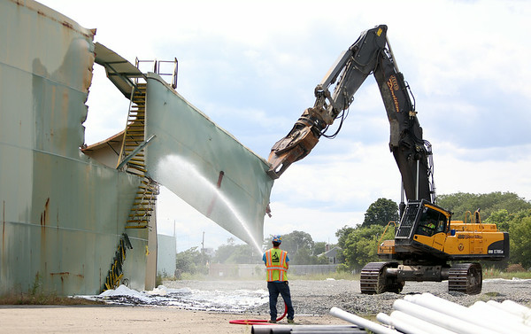 An excavator with a shearing mechanism attached, operated by a member of JDC Demolition, rips off a section of the outer wall of the B5 tank, an old oil tank inside the Salem Power Plant facility on Wednesday afternoon. The B5 tank is the first of the old oil tanks on the site to be taken down and will take approximately two weeks until it is completely gone. DAVID LE/Staff photo. 7/30/14.