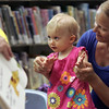 KEN YUSZKUS/Staff photo. Bridget Burke, 14 months, participates in the Wee Folks program at the Abbot Public Library with help from her mother Barbara.     7/11/14