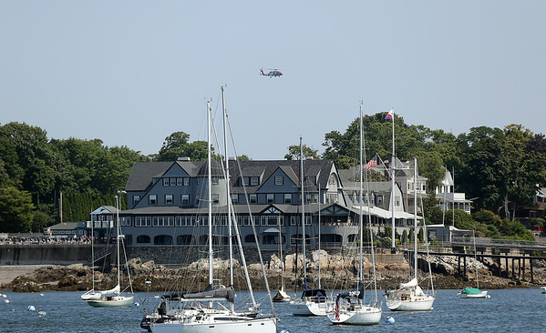 A Coast Guard chopper patrols the skies over the Corinthian Yacht Club in Marblehead on Tuesday afternoon after a diver went missing near Children's Island on Tuesday morning. DAVID LE/Staff photo. 7/22/14.