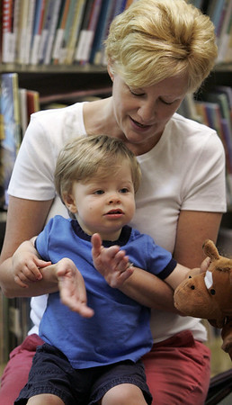 KEN YUSZKUS/Staff photo. Jimmy Servello, 16 months, participates in the sing along portion of the Wee Folks program at the Abbot Public Library with his mother Debby.     7/11/14