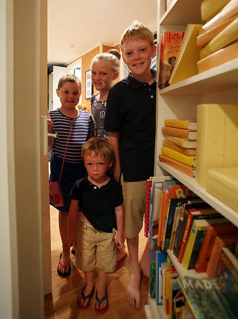 Riley Fessenden, 7, with her siblings Meghan, 8, Drew, 10, and Daniel, 2, peek through their new secret doorway hidden behind a bookshelf inside their new playroom. With the help of 75 volunteers, a nonprofit called Special Spaces Boston, did a three-day makeover of the downstairs playroom for Riley Fessenden and her brothers and sisters. DAVID LE/Staff photo. 7/26/14.